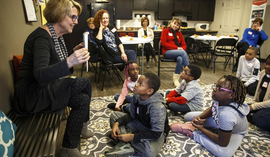 """In this Jan. 23, 2018 photo, Sue Manson, left, reads the children's book """"The Mitteen Tree"""" for  the kids as their first activity after arriving for the after school program for youth living in the Boulevard Townhomes, put on by retired teachers at the housing complex, in Springfield, Ill. Tutoring children isn't how Manson and the group of other retired teachers envisioned their retirement. But spending two hours on Tuesday afternoons, the teachers said, has helped them rediscover why they fell in love with teaching in the first place, helping kids. (Justin L. Fowler/The State Journal-Register via AP)"""