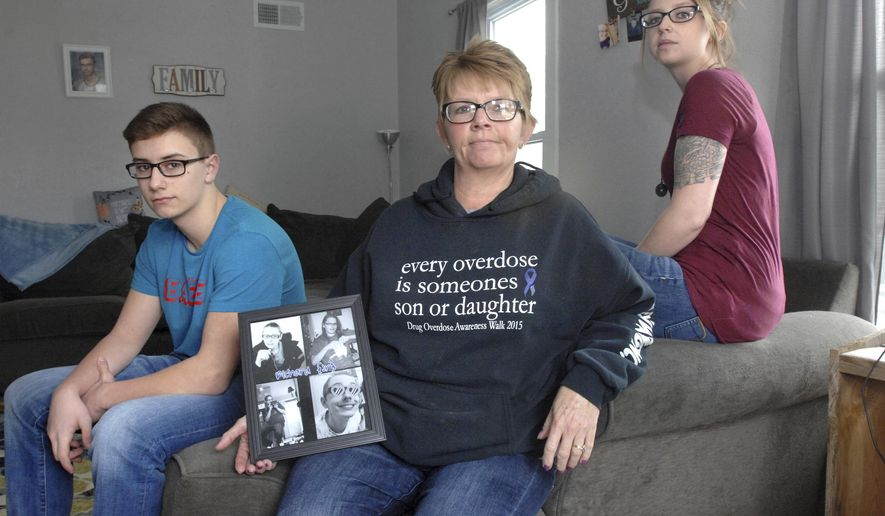 "In this 2018 photo, Richard ""Duney"" Long's family poses with his photograph at the family's  Canton, Ill., home. At right is his sister, Jessica Kinsel, in the center is his mother, Sue Tisdale, and at left is is son, Ethan Long, who also lost his mother to opioid overdose several years after his father's death. Tisdale and Kinsel founded Duney's Defense shortly after Richard Long died in 2015 to address the growing opioid epidemic in Fulton County, and today they are working for the Human Service Center in Peoria to educate people in 28 counties in Illinois about opioids. (Leslie Renken/Journal Star via AP)"