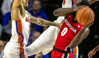 Florida guard Chris Chiozza (11) pressures Georgia guard William Jackson II (0) during the first half of an NCAA college basketball game in Gainesville, Fla., Wednesday, Feb. 14, 2018. (Alan Youngblood/The Gainesville Sun via AP)