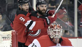 New Jersey Devils right wing Kyle Palmieri (21) celebrates his goal with left wing Taylor Hall (9) as Carolina Hurricanes goaltender Scott Darling (33) reacts during the second period of an NHL hockey game Thursday, Feb. 15, 2018, in Newark, N.J. (AP Photo/Bill Kostroun)