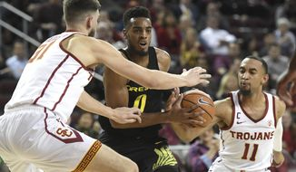 Oregon forward Troy Brown (0) drives against Southern California's Nick Rakocevic, left, and Jordan McLaughlin (11) during the first half of an NCAA college basketball game, Thursday, Feb. 15, 2018, in Los Angeles. (AP Photo/Michael Owen Baker)