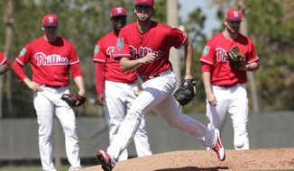 Philadelphia Phillies starting pitcher Aaron Nola works on a drill during baseball spring training camp, Thursday, Feb. 15, 2018, in Clearwater, Fla. (AP Photo/Lynne Sladky)