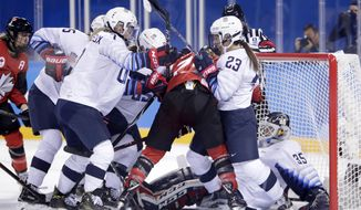 United States goalie Maddie Rooney, far right, falls into her net as teammates compete for the puck with Canada players during the first period of a preliminary round during a women's hockey game at the 2018 Winter Olympics in Gangneung, South Korea, Thursday, Feb. 15, 2018. (AP Photo/Julio Cortez)