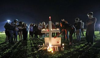 A woman places a poster of shooting victim Meadow Pollack, at one of seventeen crosses, after a candlelight vigil for the victims of the Wednesday shooting at Marjory Stoneman Douglas High School, in Parkland, Fla., Thursday, Feb. 15, 2018. Nikolas Cruz, a former student, was charged with 17 counts of premeditated murder on Thursday. (AP Photo/Gerald Herbert)