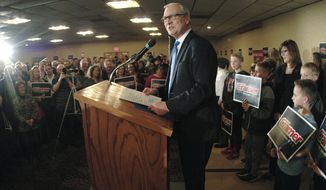 U.S. Rep. Kevin Cramer, R-N.D., center, makes his official announcement to run for a U.S. Senate seat in front of a ballroom full of supporters at a local hotel Friday, Feb. 16, 2018, in Bismarck, N.D. Cramer's wife Kris, back right, looks on. Cramer will campaign against incumbent Sen. Heidi Heitkamp, D-N.D. (Mike McCleary/The Bismarck Tribune via AP)