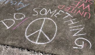 """This Friday, Feb. 16, 2018 photo shows messages written by a group of Plant High School seniors on the sidewalk leading to their school in Tampa, Fla. """"In addition to thoughts and prayers, action and policy need to take order,"""" said senior Catarina Sterlacci. (James Borchuck/The Tampa Bay Times via AP)"""