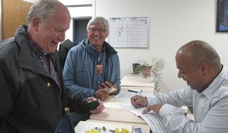 FILE - In this Aug. 21, 2017 file photo, Alaska Gov. Bill Walker, left, and Lt. Gov. Byron Mallott, center, smile as they complete paperwork to see re-election at the state Division of Elections in Juneau, Alaska. Alaska Gov. Bill Walker holds an early fundraising edge in his bid for re-election this year. Records filed with the state show Walker had about $50,000 in carry-over campaign cash and raised another roughly $275,000 since last February. (AP Photo/Becky Bohrer, File)