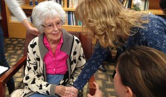 FILE - In this Feb. 16, 2017, file photo, Annie Glenn, widow of astronaut and U.S. Sen. John Glenn, speaks to a staff member of the Ohio State University John Glenn College of Public Affairs at a party for her 97th birthday, which is Friday, in Columbus, Ohio. Admirers of Glenn will be able to watch a videotaped 98th birthday tribute to her online and leave the widow of astronaut John Glenn well wishes. A spokesman for the college of public affairs said faculty and staff will tape the greeting Friday, Feb. 16, 2018, at a private birthday celebration in her honor. (AP Photo/Julie Carr Smyth, File)