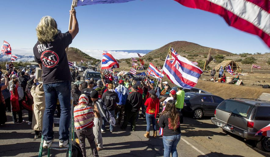 """FILE - In this June 24, 2015 file photo, Thirty Meter Telescope protesters walk on a road during a blockade that prevented TMT construction vehicles from driving up to the summit of Mauna Kea near Hilo on the island of Hawaii in Hawaii. In a similar vein, Native Hawaiian activists, who claim to be descendants of Kauai's last king, are occupying the closed Coco Palms Hotel on the island of Kauai, saying they have documents giving them the rights to the land, and are protesting the rebuilding of the hotel, where Elvis Presley's character got married in the film """"Blue Hawaii."""" It has been closed since a hurricane tore through it in 1992. (Holly Johnson/Hawaii Tribune-Herald via AP, File)"""