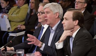 FILE- In this Feb. 7, 2018 file photo, Gov. Rick Snyder, center, speaks flanked by State Budget Director John Walsh, left, and Lt. Gov. Brian Calley, right, while presenting the state budget in Lansing, Mich. To boost base K-12 funding by the largest amount in 17 years, Snyder wants to cut funding to cyber schools and curtail funding for public schools that teach non-core classes to private school students. (Dale G.Young/Detroit News via AP)