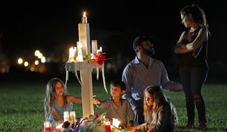 Rich and Rachel Castleberry visit one of seventeen crosses after a candlelight vigil for the victims of the Wednesday shooting at Marjory Stoneman Douglas High School, in Parkland, Fla., Thursday, Feb. 15, 2018. Nikolas Cruz, a former student, was charged with 17 counts of premeditated murder on Thursday. With them are their children Mila, 9, left, Jack, 5, center, and Lucy, 7. (AP Photo/Gerald Herbert)