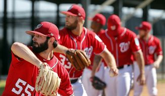 Washington Nationals pitchers, including Tim Collins (55) and Matt Grace (33) throw in the bullpen during spring training baseball practice Saturday, Feb. 17, 2018, in West Palm Beach, Fla. (AP Photo/Jeff Roberson) ** FILE **