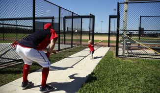 Washington Nationals outfielder Adam Eaton tosses a ball to his son, Brayden, during spring training baseball practice Saturday, Feb. 17, 2018, in West Palm Beach, Fla. (AP Photo/Jeff Roberson)