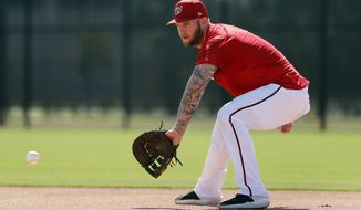 Washington Nationals infielder Matt Adams handles a grounder during spring training baseball practice Saturday, Feb. 17, 2018, in West Palm Beach, Fla. (AP Photo/Jeff Roberson) **File**