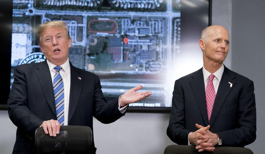 President Donald Trump, left, accompanied by Florida Gov. Rick Scott, right, speaks as they meet with law enforcement officers at Broward County Sheriff's Office in Pompano Beach, Fla., Friday, Feb. 16, 2018, following Wednesday's shooting at Marjory Stoneman Douglas High School, in Parkland, Fla. (AP Photo/Andrew Harnik)