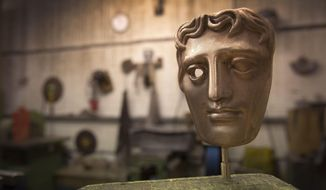 FILE - In this Tuesday, Jan. 31, 2017 file photo, a bronze alloy BAFTA mask stands in a foundry in West Drayton, London, ahead of the award ceremony in February. Designed by US sculptor Mitzi Cunliffe in 1955, New Pro Foundries has been making the bronze casts since the ceremony was created in 1976. The red carpet will be a sea of black as the movement against sexual misconduct takes center stage at the British Academy Film Awards on Sunday Feb. 18, 2018. (Photo by Joel Ryan/Invision/AP, File)