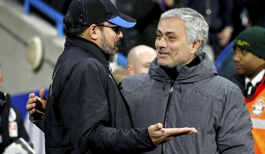 Huddersfield Town manager David Wagner, left, and Manchester United manager Jose Mourinho speak before the English FA Cup, fifth round soccer match at The John Smith's Stadium, Huddersfield, England, Saturday Feb. 17, 2018. (Martin Rickett/PA via AP)