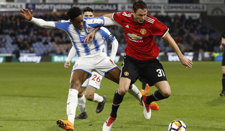Manchester United's Nemanja Matic, left, and Huddersfield Town's Terence Kongolo battle for the ball during the English FA Cup, fifth round soccer match at The John Smith's Stadium, Huddersfield, England, Saturday Feb. 17, 2018. (Martin Rickett/PA via AP)