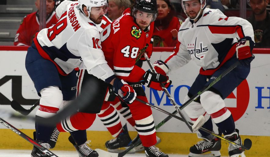 Chicago Blackhawks left wing Vinnie Hinostroza (48) looks to pass the puck past Washington Capitals center Chandler Stephenson (18) during the second period of an NHL hockey game Saturday, Feb. 17, 2018, in Chicago. (AP Photo/Jeff Haynes)