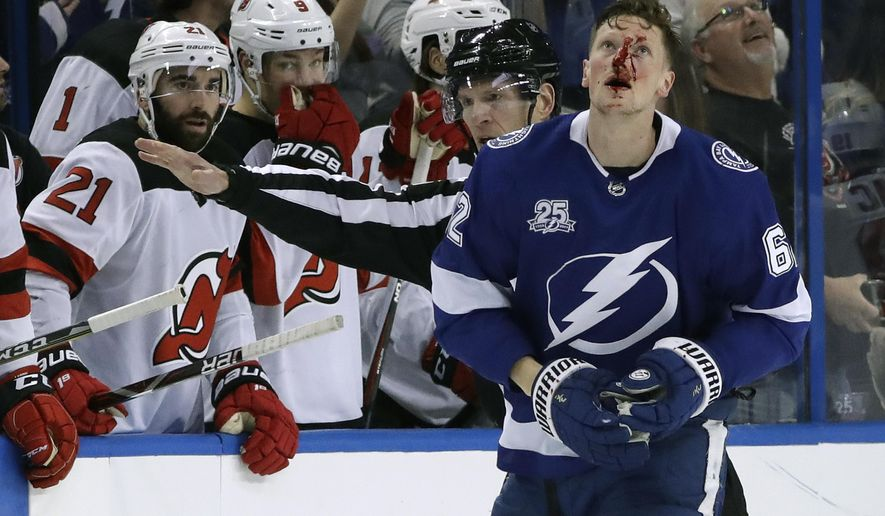 Tampa Bay Lightning defenseman Andrej Sustr (62) is covered in blood as he leaves the ice after getting into a scrap with New Jersey Devils left wing Miles Wood during the second period of an NHL hockey game Saturday, Feb. 17, 2018, in Tampa, Fla. (AP Photo/Chris O'Meara)