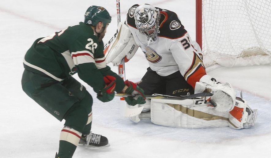 Anaheim Ducks' goalie John Gibson, right, stops a shot as Minnesota Wild's Daniel Winnik positions himself for a rebound in the second period of an NHL hockey game Saturday, Feb. 17, 2018, in St. Paul, Minn. (AP Photo/Jim Mone)