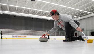 ADVANCE FOR USE SATURDAY, FEB. 17 - In this Jan. 16, 2018 photo, Logun Gunderson practices throwing a stone while using a broom for balance during University of Nebraska-Lincoln Curling Club practice at John Breslow Ice Hockey Center in Lincoln, Neb. (Gwyneth Roberts/The Journal-Star via AP)