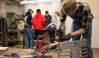 ADVANCE FOR USE SATURDAY FEB. 17 - In this Feb. 1, 2018 photo, Kiel Kruse works on restoring the grill to a 1946 John Deere Model 69 Prototype M at the University of Nebraska Tractor Restoration Club's shop  in Lincoln, Neb. (Ryan Soderlin/Omaha World-Herald via AP)