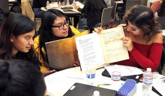 In this Wednesday, Feb. 14, 2018 photo, Pasco High School students Cynthia Cisneros, left, and Belen Trinidad, center, listen as Maria Duvon explains what she highlighted in her Hamilton work packet inside the school's library in Pasco, Wash. Pasco High School was selected by the Gilder Lehrman Institute to participate in their Hamilton Education Program. A hundred juniors were nominated by their teachers and must complete the lesson plan and turn in a final project in order to see Hamilton in Seattle. (Noelle Haro-Gomez/The Herald via AP)/The Tri-City Herald via AP)