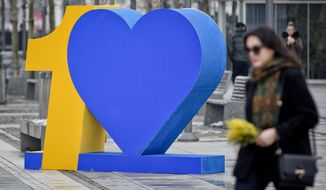 Kosovars walk past number ten sign marking the 10th anniversary of Kosovo independence on Wednesday Feb. 14, 2018, ahead of the upcoming 10th independence anniversary. (AP Photo/Visar Kryeziu)