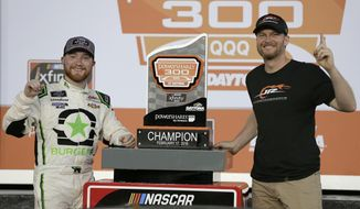 Tyler Reddick, left, and team owner Dale Earnhardt Jr., right, pose with the trophy in Victory Lane after winning the NASCAR Xfinity series auto race at Daytona International Speedway in Daytona Beach, Fla., Saturday, Feb. 17, 2018. (AP Photo/Terry Renna)