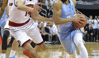 North Carolina guard Joel Berry II (2) drives the lane against the defense of Louisville forward Anas Mahmoud (14) during the first half of an NCAA college basketball game, Saturday, Feb. 17, 2018, in Louisville, Ky. (AP Photo/Timothy D. Easley)