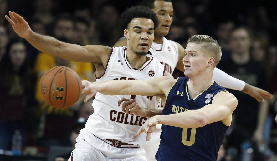 Notre Dame's Rex Pflueger (0) passes off as Boston College's Jerome Robinson defends during the first half of an NCAA college basketball game in Boston, Saturday, Feb. 17, 2018. (AP Photo/Michael Dwyer)