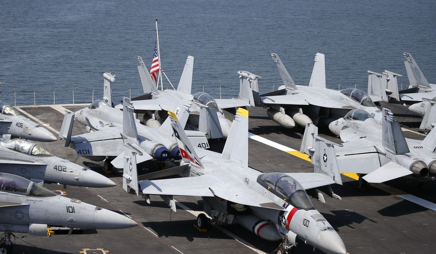 U.S. military aircraft sit on the deck of the USS Carl Vinson aircraft carrier anchors off Manila, Philippines, for a five-day port call along with guided-missile destroyer USS Michael Murphy, Saturday, Feb. 17, 2018. Lt. Cmdr. Tim Hawkins told The Associated Press that American forces will continue to patrol the South China Sea wherever international law allows when asked if China's newly built islands could restrain them in the disputed waters. (AP Photo/Bullit Marquez)