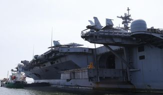 U.S. military aircraft sit on the flight deck of the USS Carl Vinson aircraft carrier anchors off Manila, Philippines, for a five-day port call along with guided-missile destroyer USS Michael Murphy, Saturday, Feb. 17, 2018. U.S. Lt. Cmdr. Tim Hawkins told The Associated Press that American forces will continue to patrol the South China Sea wherever international law allows when asked if China's newly built islands could restrain them in the disputed waters. (AP Photo/Bullit Marquez) ** FILE **