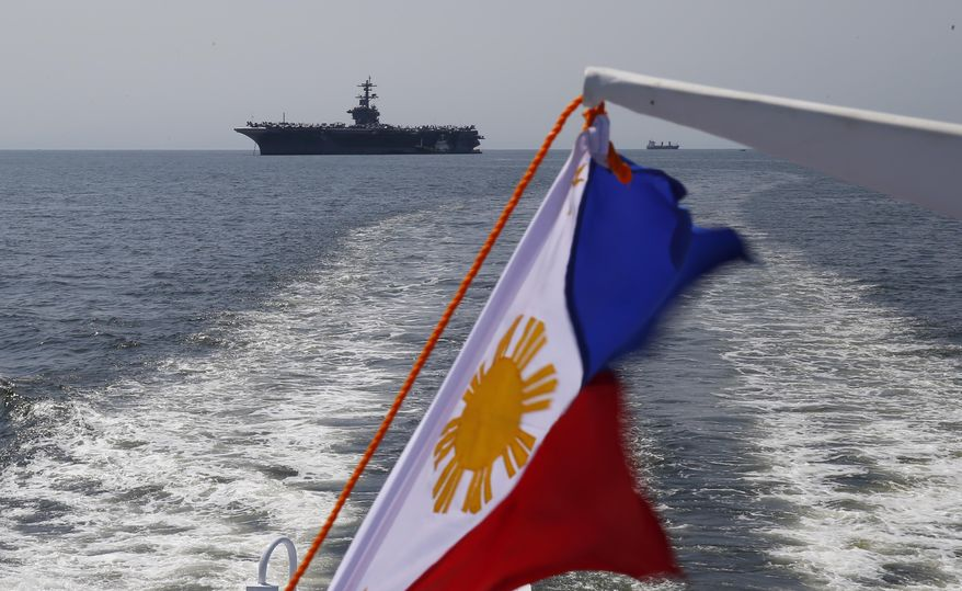 "The aircraft carrier USS Carl Vinson left a four-day port visit in the Philippines on Tuesday and is leading a strike group to conduct a ""freedom of navigation operation"" in the South China Sea. (Associated Press)"