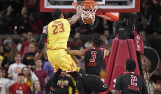 Maryland forward Bruno Fernando (23) dunks over Rutgers guard Corey Sanders (3) and center Shaquille Doorson (2) during the first half of an NCAA college basketball game Saturday, Feb. 17, 2018, in College Park, Md. (AP Photo/Nick Wass)