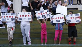 A group of people hold signs that read 'Guns Down Test Scores UP' during a protest against guns on the steps of the Broward County Federal courthouse in Fort Lauderdale, Fla., on Saturday, Feb. 17, 2018. Nikolas Cruz, a former student, is charged with killing 17 people at Marjory Stoneman Douglas High School in Parkland, Fla., on Wednesday. (AP Photo/Brynn Anderson)