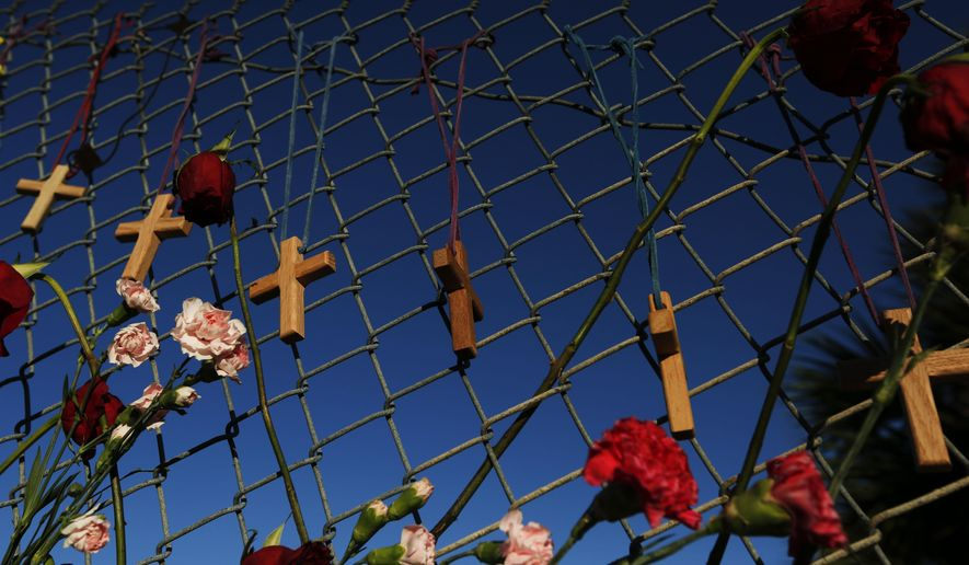 Crosses and flowers hang on a fence near Majority Stoneman Douglas High School, near Parkland, Fla., on Saturday, Feb. 16, 2018, in memory of the 17 people killed in a school shooting on Wednesday.  As families began burying their dead, authorities questioned whether they could have prevented the attack at the high school where a gunman, Nikolas Cruz, took several lives. (AP Photo/Brynn Anderson)