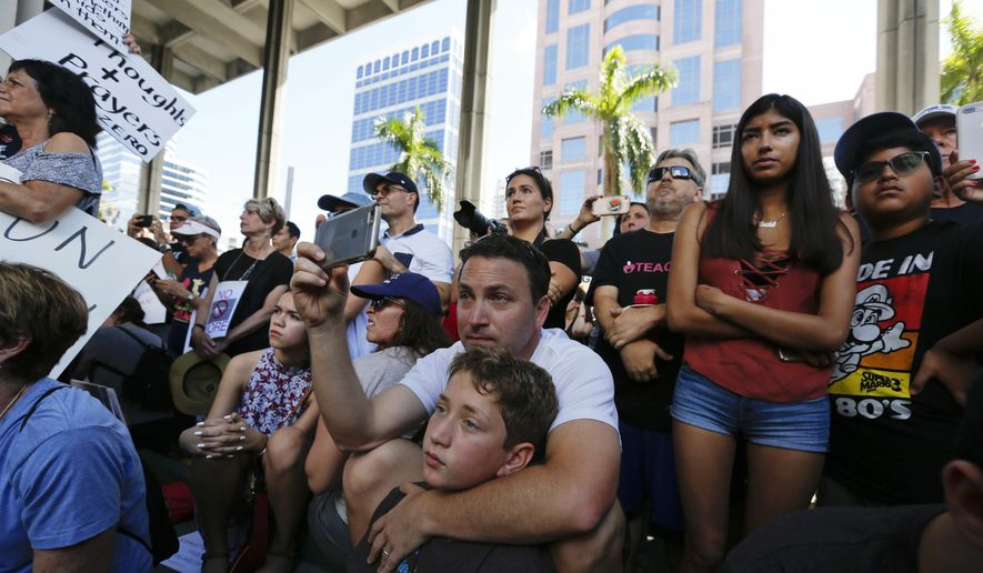 Louis Reinstein, embraces his son, Daniel, 10, during a protest against guns on the steps of the Broward County Federal courthouse in Fort Lauderdale, Fla., on Saturday, Feb. 17, 2018. Nikolas Cruz, a former student, is charged with killing 17 people at Marjory Stoneman Douglas High School in Parkland, Fla., on Wednesday. (AP Photo/Brynn Anderson)