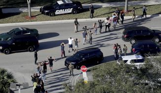 FILE - In this Feb. 14, 2018 file photo,  students hold their hands in the air as they are evacuated by police from Marjory Stoneman Douglas High School in Parkland, Fla., after a shooter opened fire on the campus.  Students are taught to evacuate during fire alarms but lock down during school shootings. So there was confusion Wednesday when a fire alarm sounded,  the second one that day at the high school as 19-year-old former student Nikolas Cruz unleashed a barrage of gunfire. Head for the exits or hunker down in classrooms? (Mike Stocker/South Florida Sun-Sentinel via AP, File)