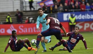 FC Barcelona's Lionel Messi competes for the ball with players from SD Eibar's Cote during the Spanish La Liga soccer match between FC Barcelona and SD Eibar, at Ipurua stadium, in Eibar, northern Spain, Saturday, Feb.17, 2018. (AP Photo/Alvaro Barrientos)