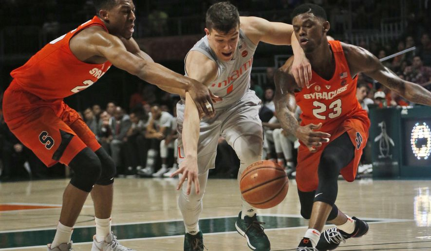 Syracuse guards Tyus Battle, left, and Frank Howard, right, battle for the ball with Miami guard Dejan Vasiljevic, center, during the first half of an NCAA college basketball game, Saturday, Feb. 17, 2018, in Coral Gables, Fla. (AP Photo/Wilfredo Lee)