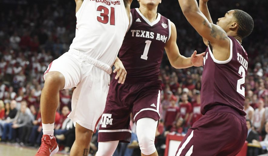 Arkansas guard Anton Beard drives to the hoop past Texas A&M defenders DJ Hogg (1) and TJ Starks (2) during the first half of an NCAA college basketball game Saturday, Feb. 17, 2018, in Fayetteville, Ark. (AP Photo/Michael Woods)