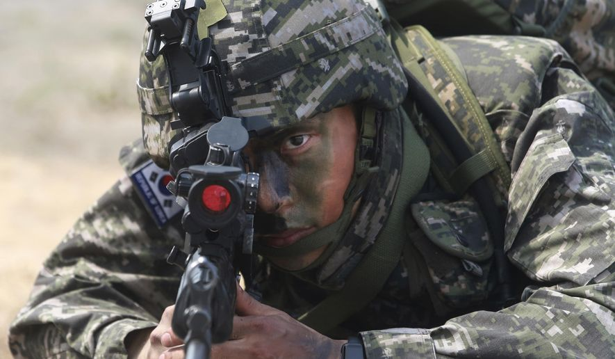 A South Korea soldier aims his machine gun during the ongoing Cobra Gold U.S.-Thai joint military exercise on Hat Yao beach in Chonburi province, eastern Thailand, Saturday, Feb. 17, 2018. Approximately 11,000 military personnel from the  U.S., Thailand, and South Korea are taking part in the annual drill. (AP Photo/Sakchai Lalit)
