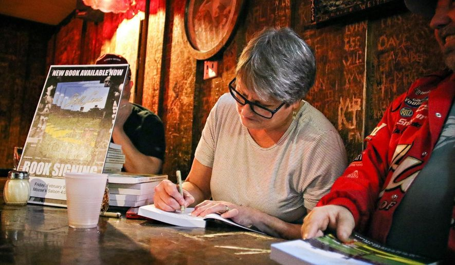 In this Feb. 9, 2018, photo, Lexie Miller Wyman signs copies of her book at Moose's Saloon in Kalispell, Mont. (Greg Lindstrom/Flathead Beacon via AP)