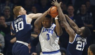 Xavier forward Tyrique Jones (0) is pressured by Villanova's Donte DiVincenzo (10) and Dhamir Cosby-Roundtree (21) during the second half of an NCAA college basketball game, Saturday Feb. 17, 2018, in Cincinnati. Villanova won 95-79. (AP Photo/Gary Landers)