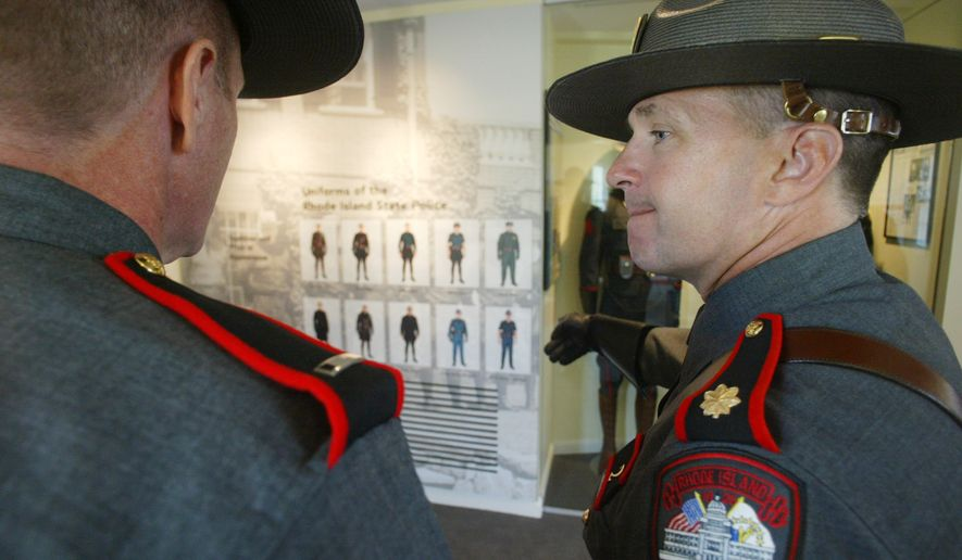 Rhode Island State Troopers Lt. Eric LaRiviere, left, and Maj. Steven O'Donnell look at a display of old uniforms at the Rhode Island State Trooper Museum, Thursday, May 18, 2006, in North Scituate, R.I.  (AP Photo/Stew Milne)