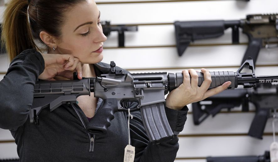 Gun shop owner Tiffany Teasdale-Causer demonstrates a Ruger AR-15 semi-automatic rifle, the same model, though in gray rather than black, used by the shooter in a Texas church massacre two days earlier, Tuesday, Nov. 7, 2017, in Lynnwood, Wash. Gun-rights supporters have seized on the Texas church massacre as proof of the well-worn saying that the best answer to a bad guy with a gun is a good guy with a gun. Gun-control advocates, meanwhile, say the tragedy shows once more that it is too easy to get a weapon in the U.S. (AP Photo/Elaine Thompson)