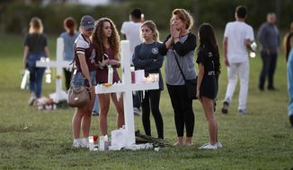 People pay homage at the memorial crosses for the 17 deceased students and faculty from the Wednesday shooting at Marjory Stoneman Douglas High School, in Parkland, Fla., Friday, Feb. 16, 2018. Nikolas Cruz, a former student, was charged with 17 counts of premeditated murder on Thursday. (AP Photo/Gerald Herbert)
