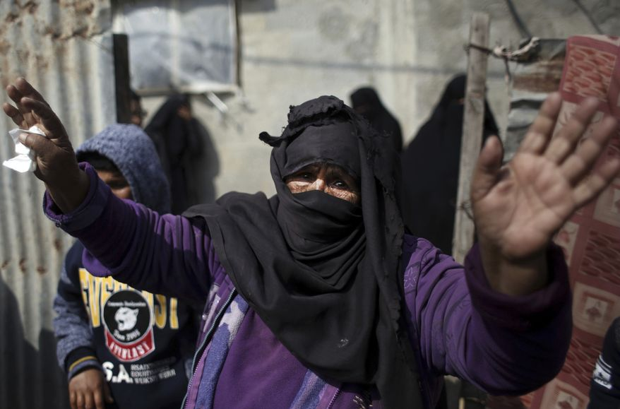 Relatives mourn one of two Palestinian teenagers who were killed Saturday trying to infiltrate Israel, during his funeral in the Rafah refugee camp, southern Gaza Strip, Sunday, Feb. 18, 2018. The Israeli military said it struck 18 targets in Gaza early on Sunday, in response to an explosive device that wounded four Israeli soldiers, along the border with the territory. (AP Photo/ Khalil Hamra)